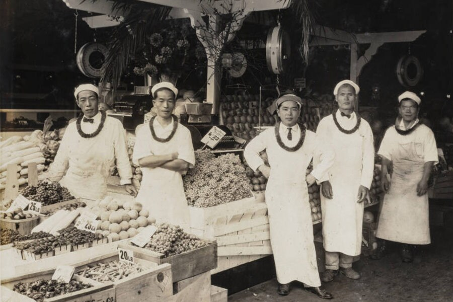 Five Japanese American men pose in front of fruit and vegetable crates at Jake's Place Market Mountain Cafe in Los Angeles, circa 1920s