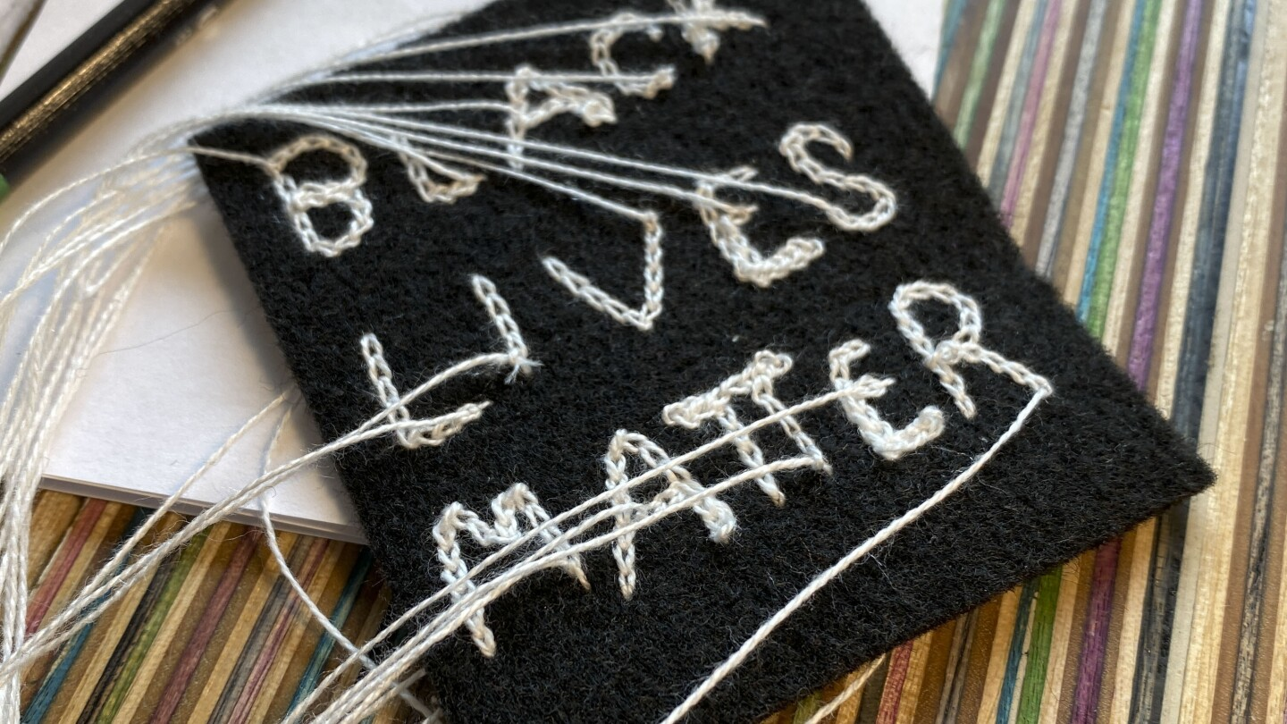 "A black, square-shaped piece of fabric with chain stitch embroidery reading the words, ""BLACK LIVES MATTER"" in white thread. The ends of the threads are long and loose. The patch sits on top of a multicolored, striped surface."