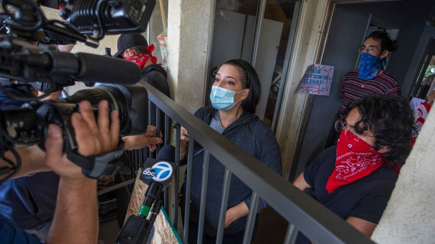 A tv camera faces a woman in a face mask from behind a fence.