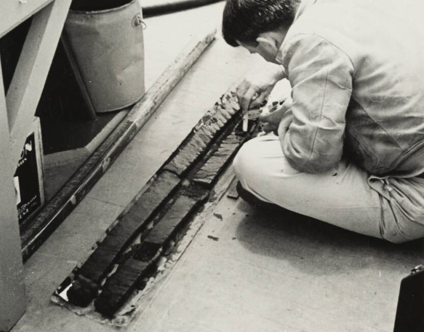 Dr. Thomas Clements examines seabed core sample, 1941. The core was obtained from a depth of several hundred fathoms by means of a coring device. | Allan Hancock Foundation Collection, USC Libraries