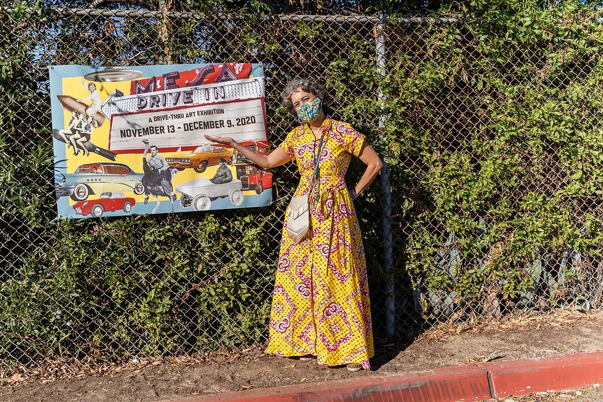"""Alessandra Moctezuma, director of the Mesa College Art Gallery by the signs of the """"Mesa College Drive-In: An Outdoor Art Exhibition"""" 