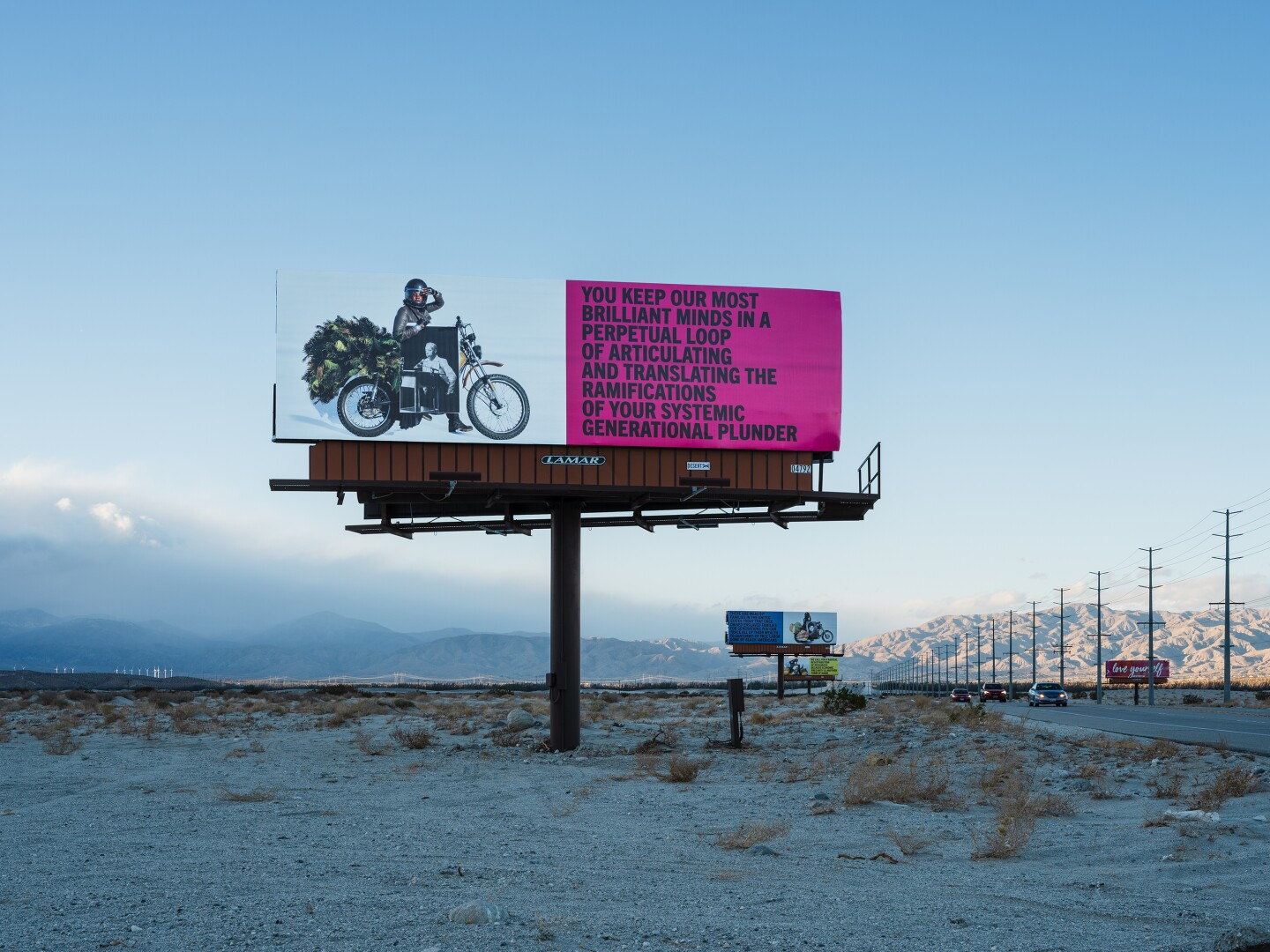"""Simmons' billboards stand along the Gene Autry Trail. The one photographed reads, """"You keep our most brilliant minds in a perpetual loop of articulating and translating the ramifications of your systemic generational plunder."""""""
