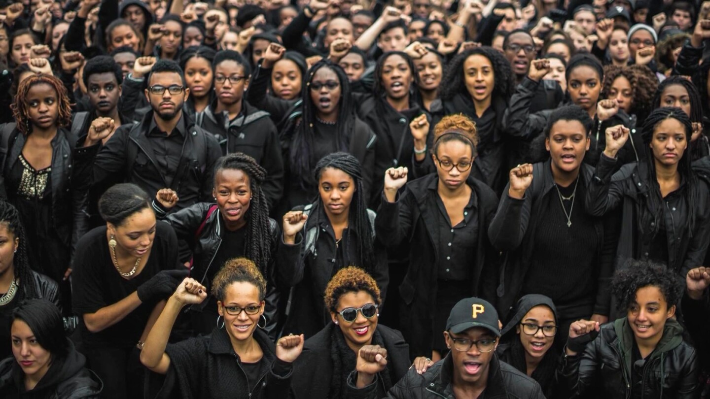 """A large crowd of young activists holding up their fists. 
