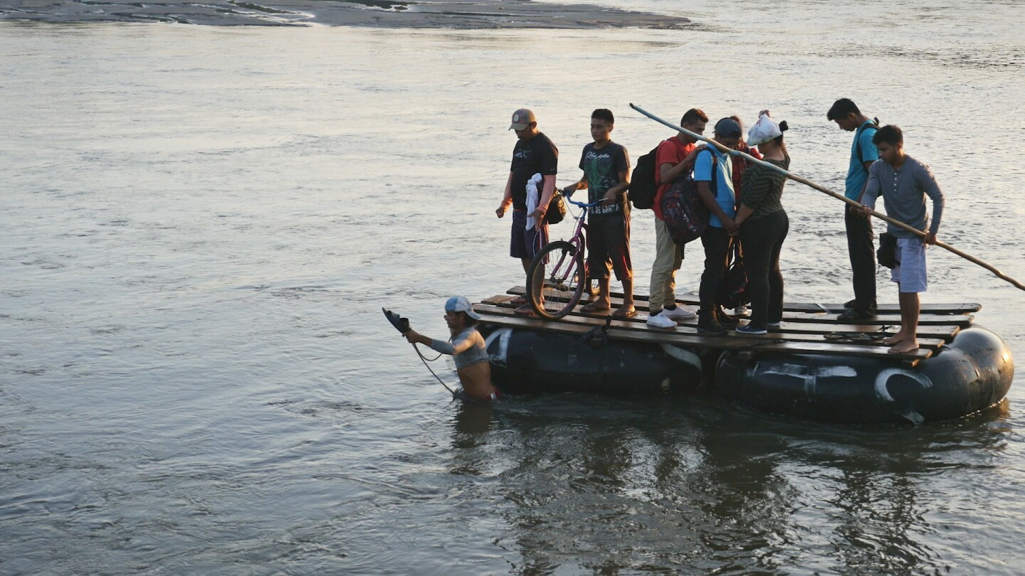 "Migrants cross a river on a raft. | Still from ""Global Mosaic"" film ""Migrant Journeys"""