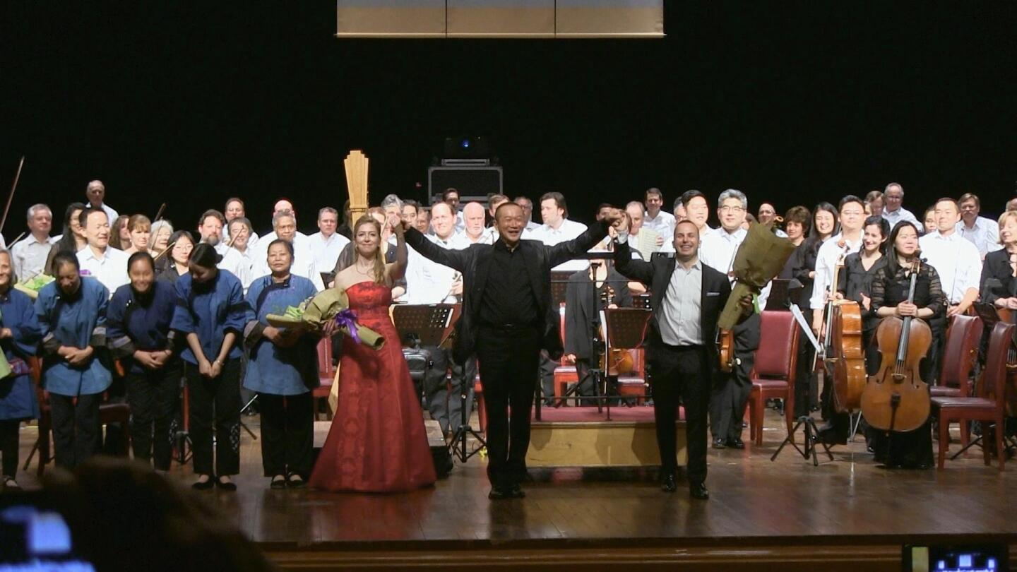 An orchestra and its conductor stand to face the audience in front of them.