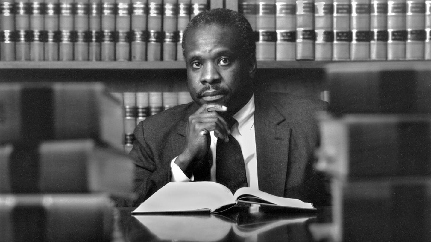 Clarence Thomas places his hand to his chin with a book open in front of him as he looks into the camera.