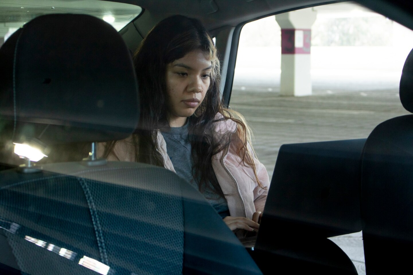 Psychology major Iris Perez completes classwork in her car in a garage at Sacramento State University onMarch 11, 2020.