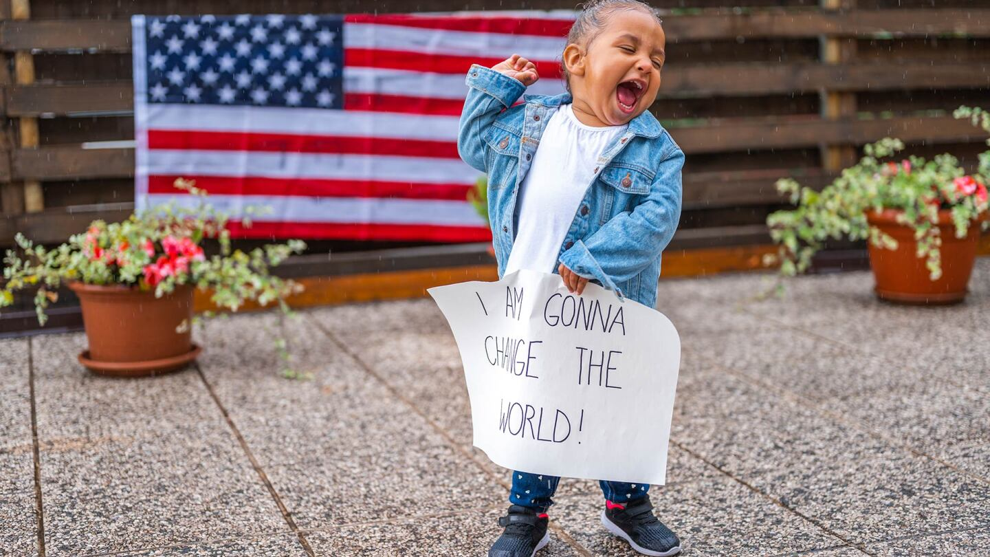 "A small child holds their fist in the air and holds a sign that reads ""I'm gonna change the world."" 