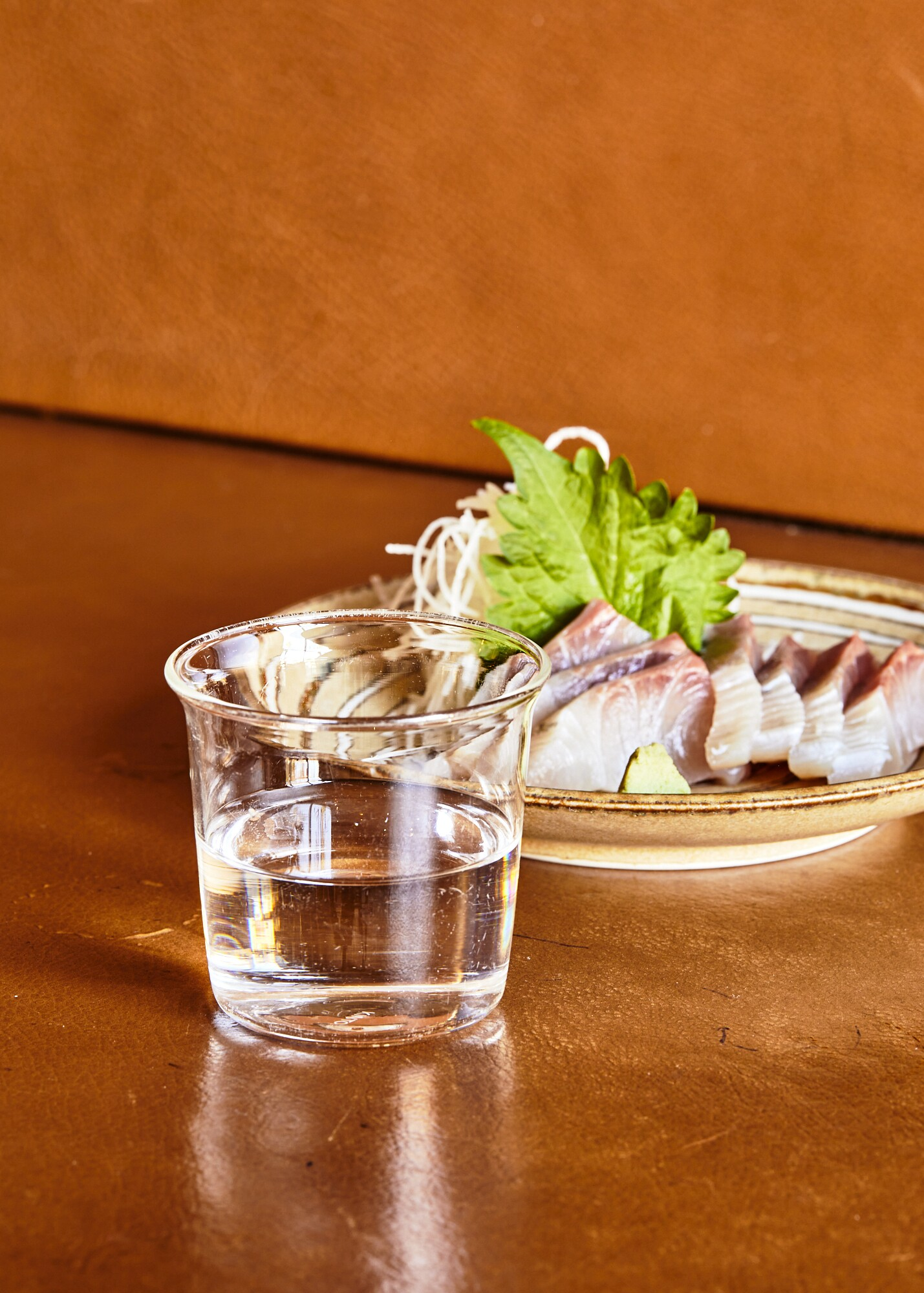 A cup of ginjo sake paired with a plate of kanpachi sashimi from Tsubaki.
