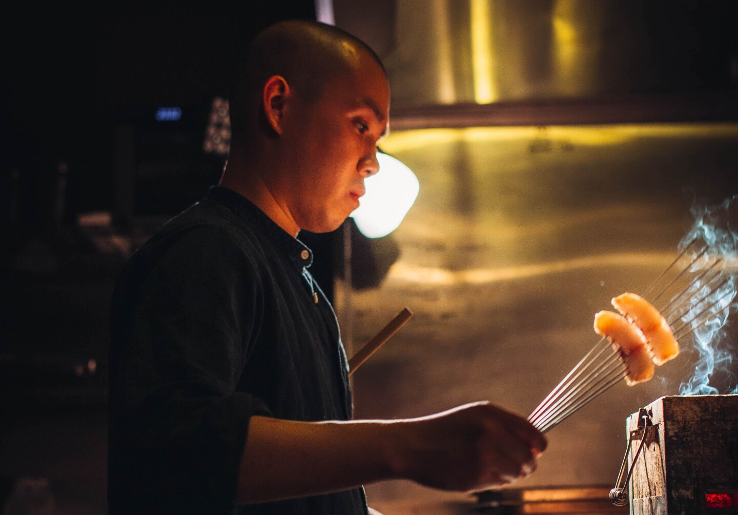 Chef Jon Yao cooks two skewered, bite-sized pieces of fish over a smokey box. He's standing in a dark kitchen and his face is lit by a warm, orange light coming from beneath him.