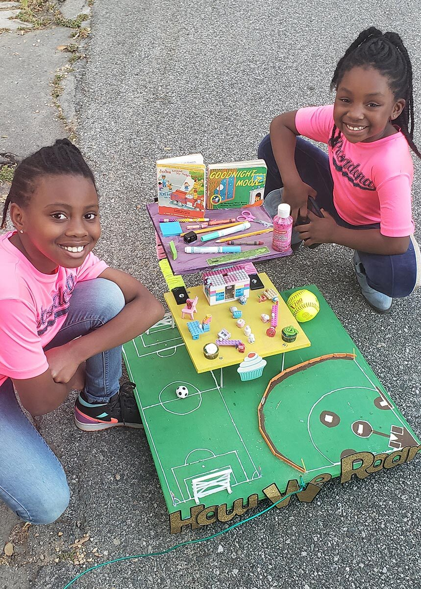 Two little girls work on a small parade float.