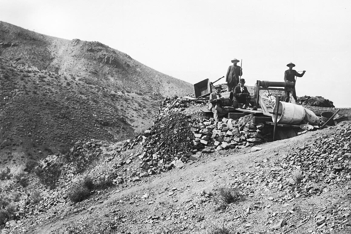Four men at the Hard Cash Mine in Randsburg, CA photographed by Charles C. Pierce, ca. 1900. The man at the right is working a windlass. | Courtesy of USC Libraries and California Historical Society.