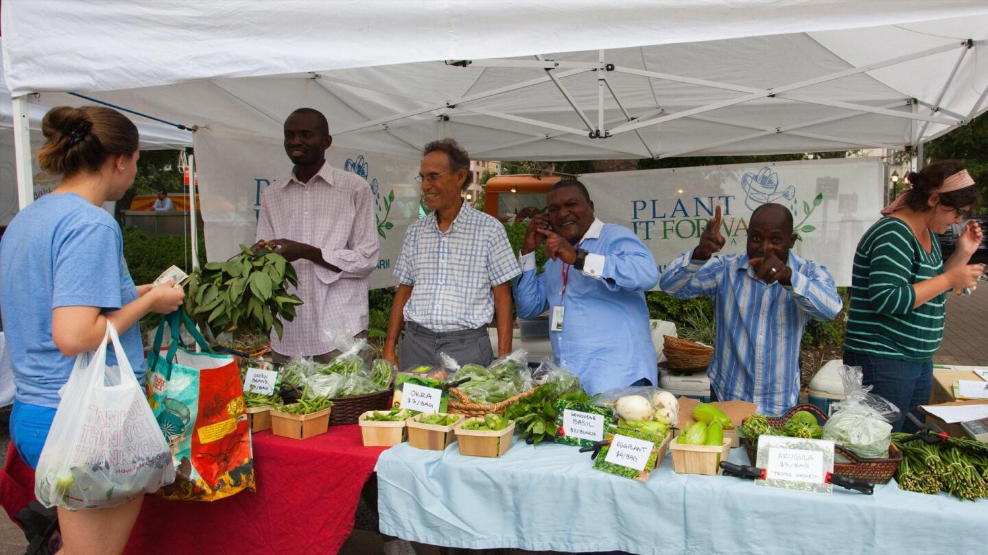 """Workers manning a """"Plant It Forward"""" food stall poses playfully for the camera."""