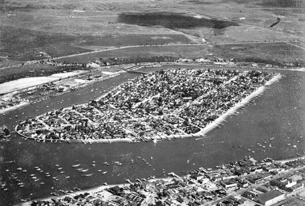An archival photo of Balboa Island, an undeveloped Orange County mainland in the background.