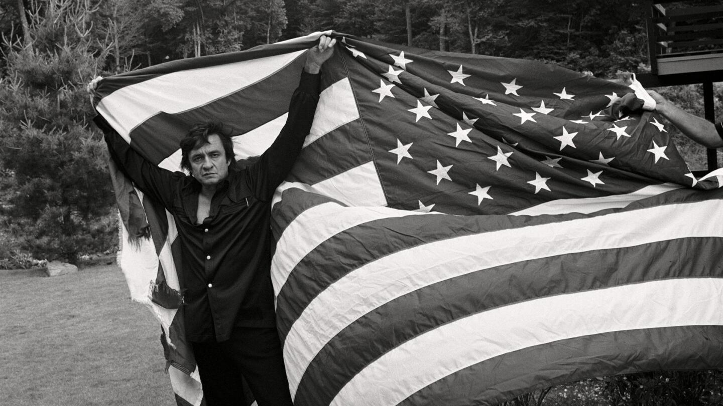 "A man uses both his arms to hoist up an American flag tapestry. | From ""Country Music: Will the Circle Be Unbroken? (1968-1972)"""