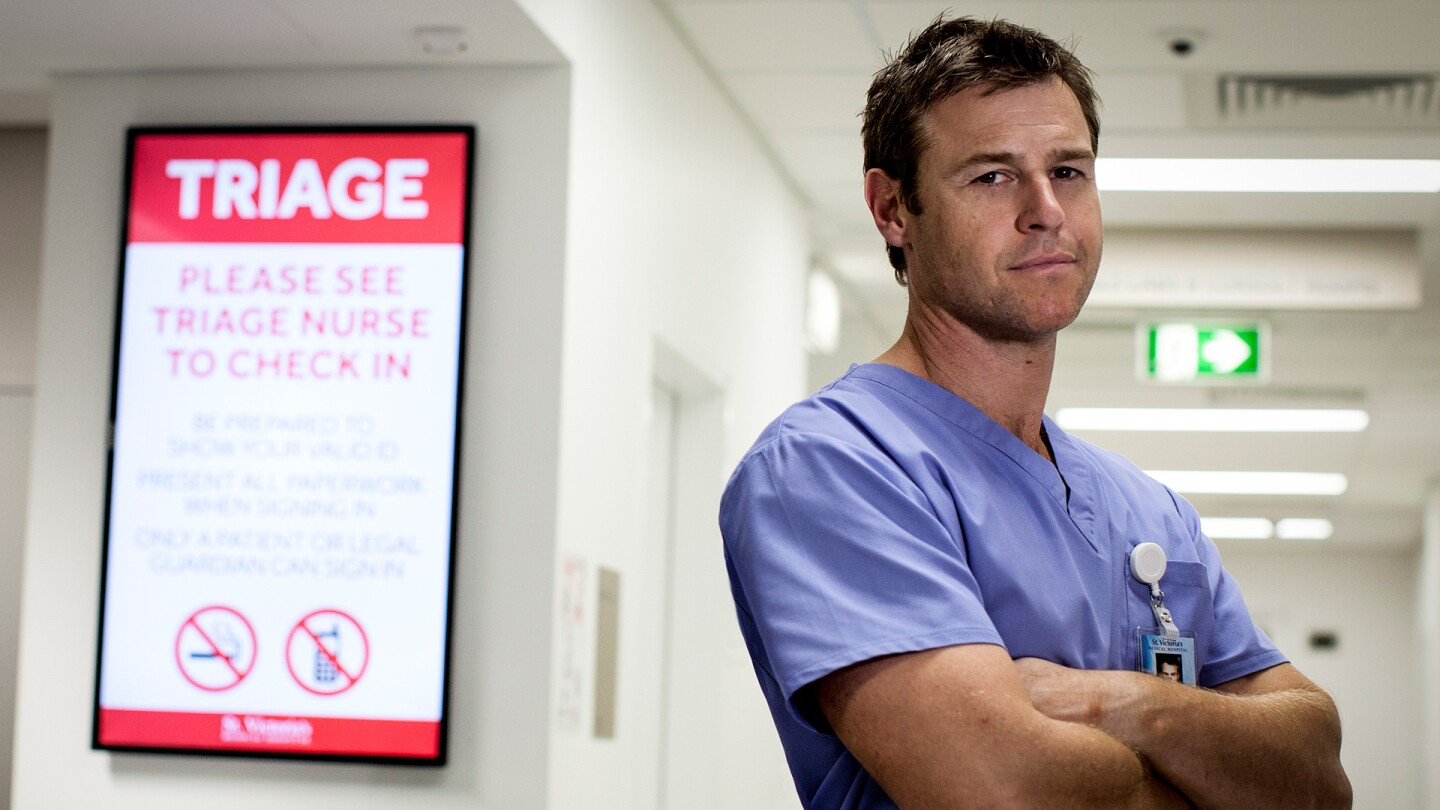 """Hugh Knight in scrubs crosses his arms. 
