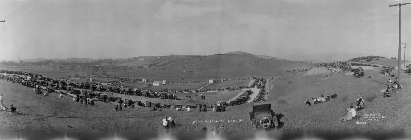A panoramic view of automobiles parked at the Legion Ascot Speedway in Los Angeles, east of downtown circa 1924. Numerous cars are parked among the low rolling hills, and people are seated and standing amongst the vehicles.
