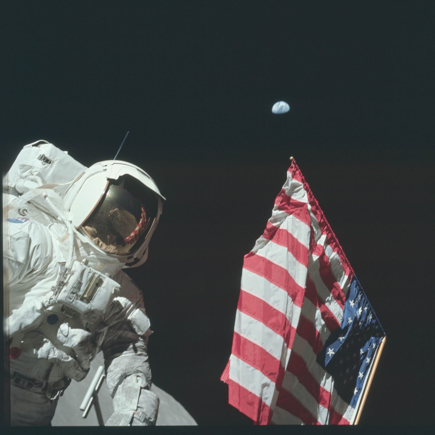 """From episode three: """"A Space Odyssey"""" Apollo 11 astronaut Buzz Aldrin plants the flag with planet Earth above, c. 1969. Courtesy NASA"""