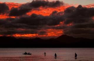 """22-cisk3 left""""> <p>ARCHIVE PHOTO: Fijian family board their canoe as a sunset lights up the sky behind an island's mountain range in Suva May 1, 2004. 
