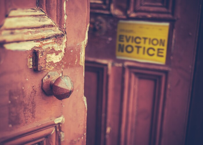 A yellow eviction notice on a brown door.