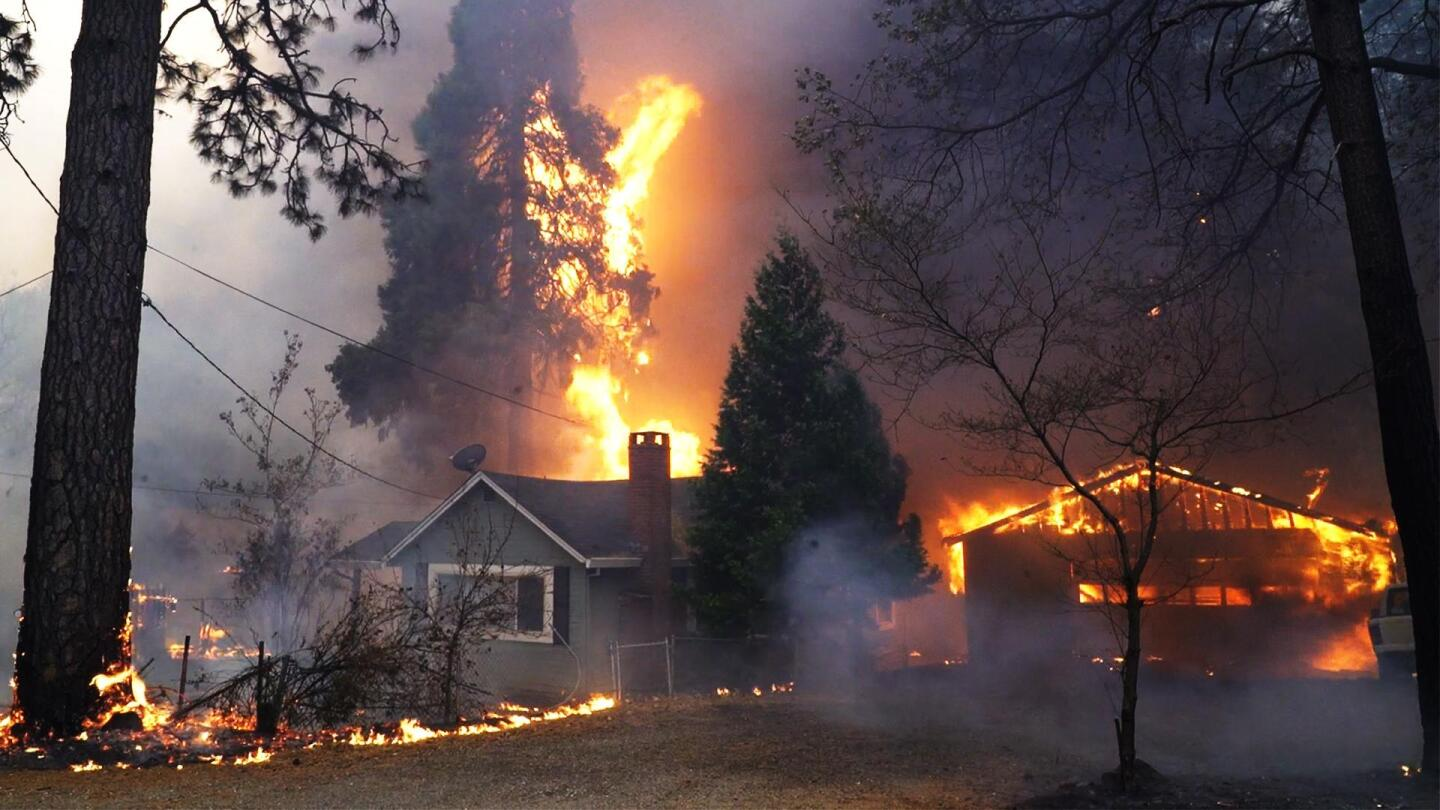 A forest fire burns homes.