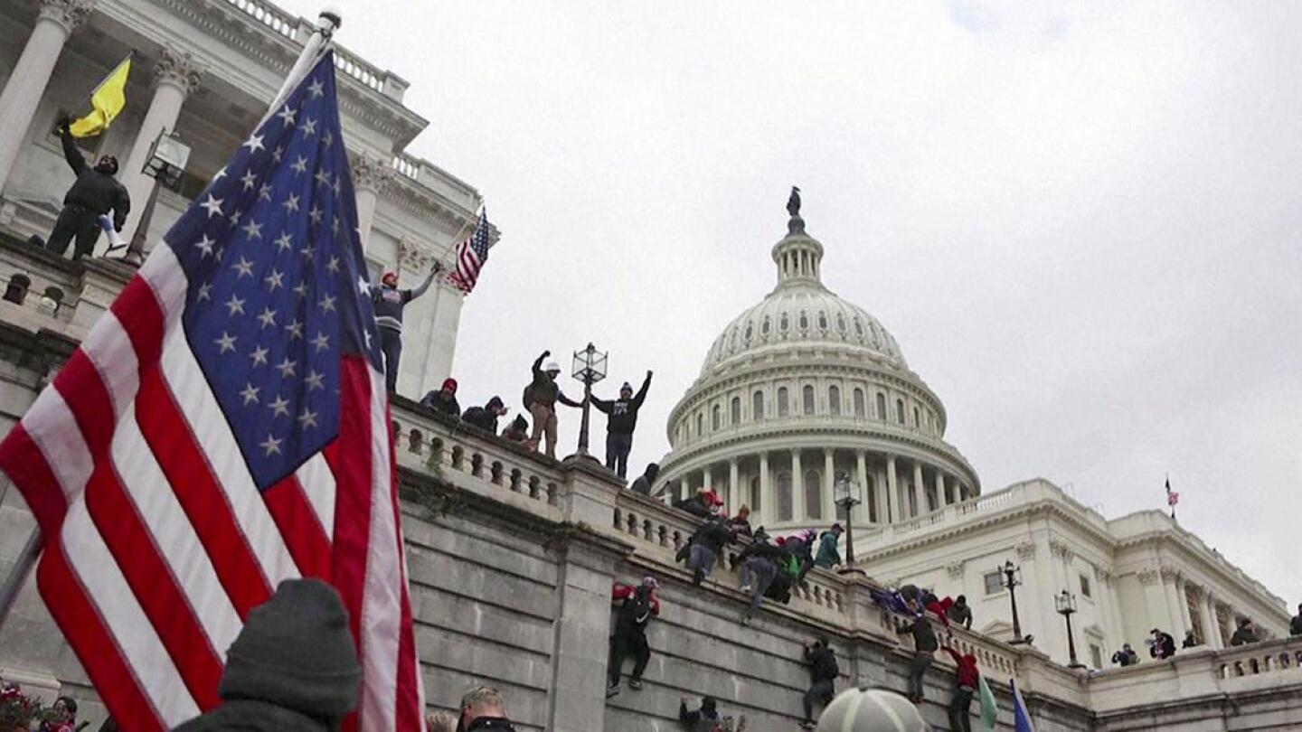 Members of a mob scale the walls outside the U.S. Capitol.