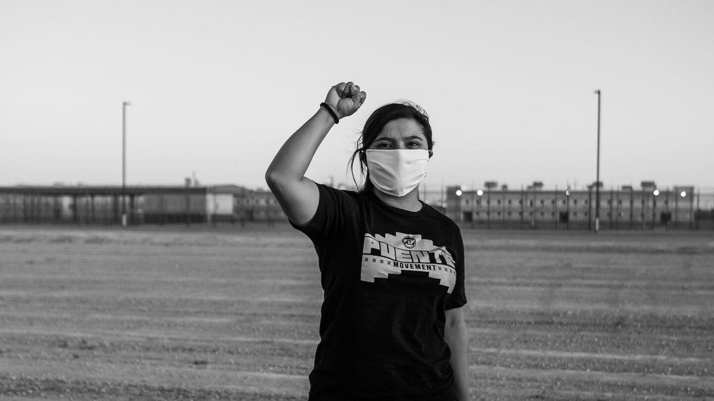"A girl wearing a mask raises her fist. | From ""Latino Vote: Dispatches from the Battleground"""