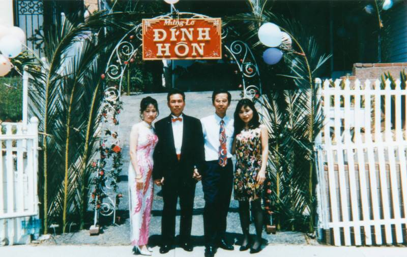 """Two couples pose in front of a sign in Vietnamese that reads """"Happy Engagement."""""""