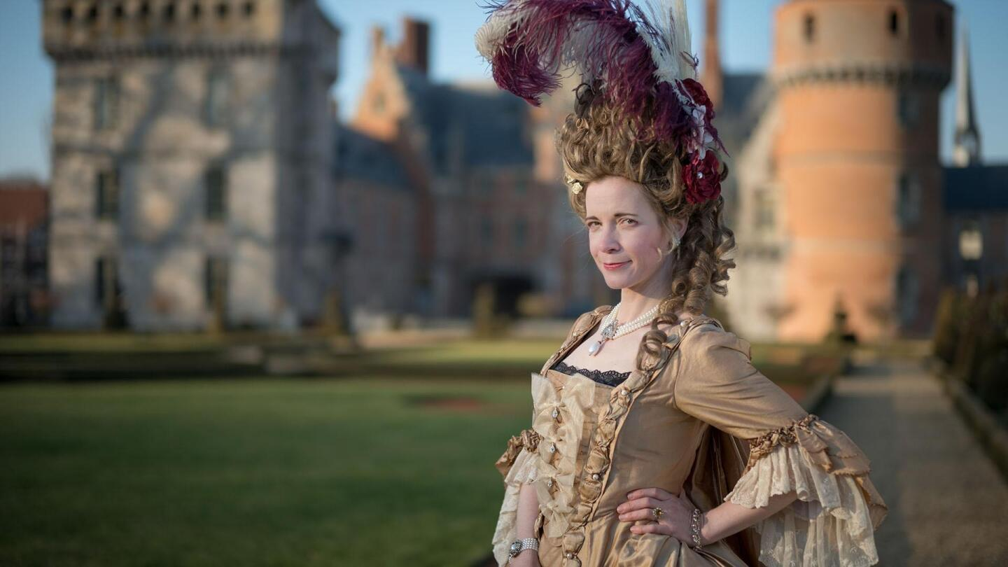 """Lucy Worsley poses with a hand on her hip while dressed as Marie Antoinette. 