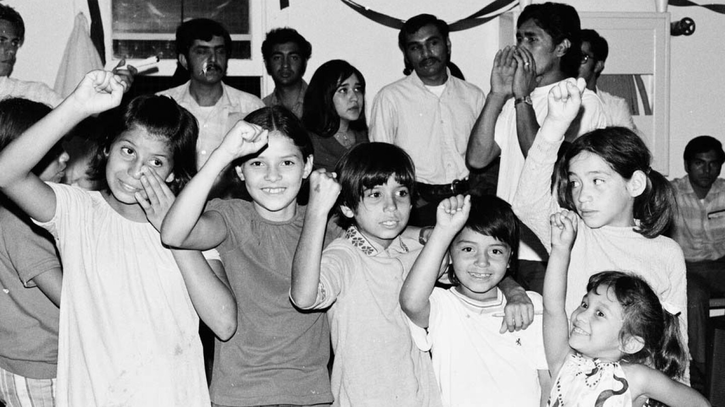 CSRC_LaRaza_B11F13C3_RR_023 Children at a musical performance by Estudiantina de la Facultad de Ingenieria from UNAM | Raul Ruiz, La Raza photograph collection. Courtesy of UCLA Chicano Studies Research Center