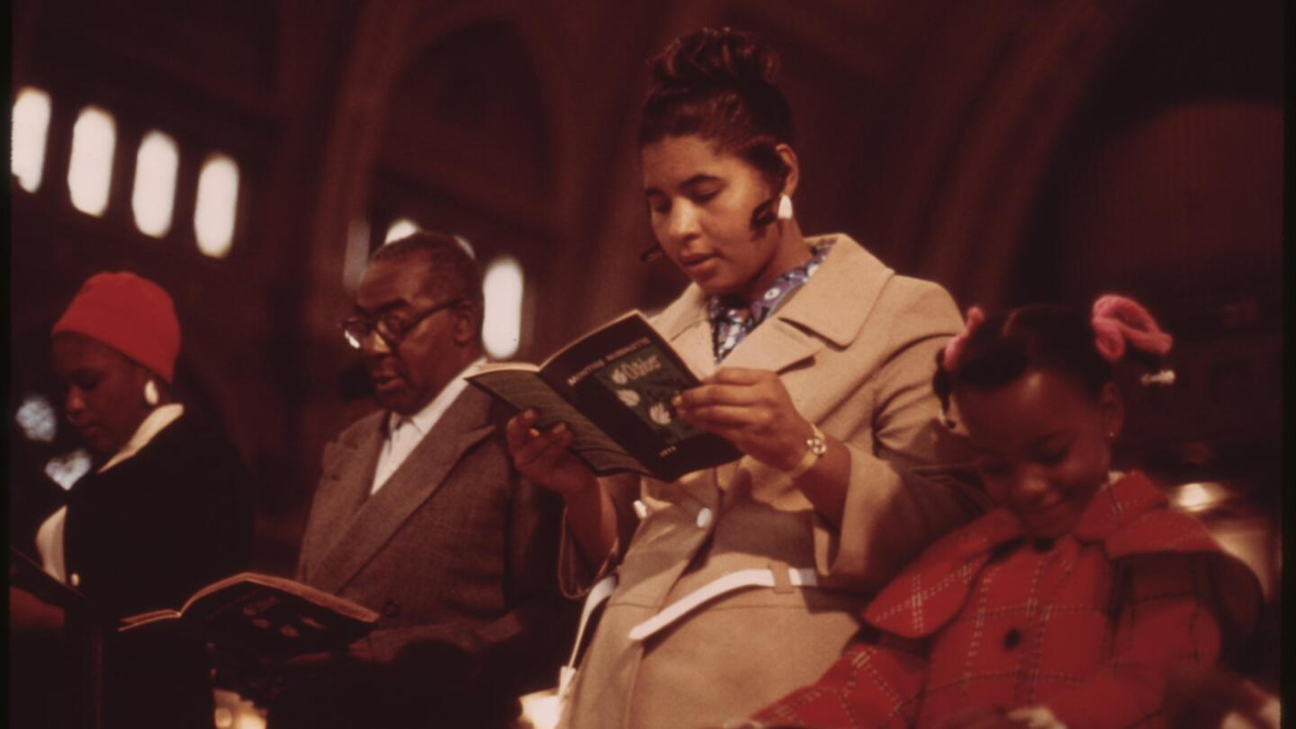 A group of people stand while reading a bible in church.
