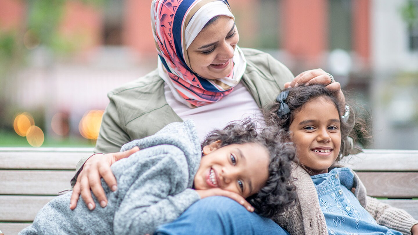 A smiling woman wearing a hijab sits with two smiling children on a bench.   stock