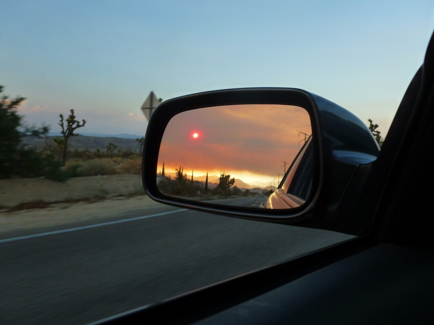 The reflection of a red sun can be seen on a car's side mirror.