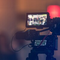 A video camera showing an image of people gathered in the frame | Kushagra Kevat/Unsplash