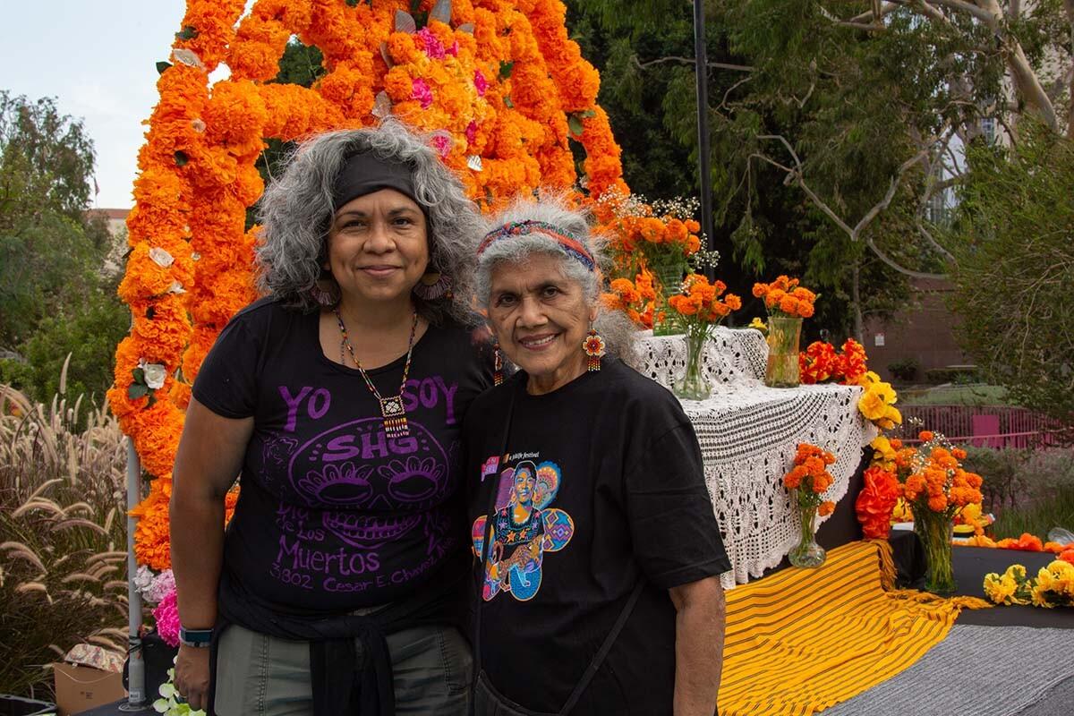 Ofelia and Rosanna Esparza of Tonalli Studio standing in front of their ofrenda at Grand Park for Día de los Muertos 2020 | Rafael Cardenas