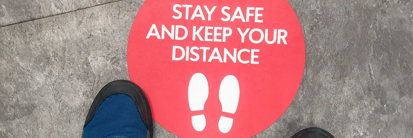 "A sticker on the ground reads ""Stay safe and keep your distance."" 