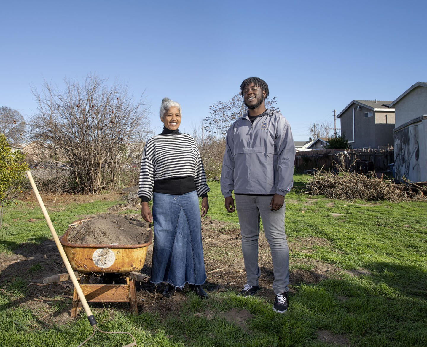 An African American man and women beside a wheelbarrow
