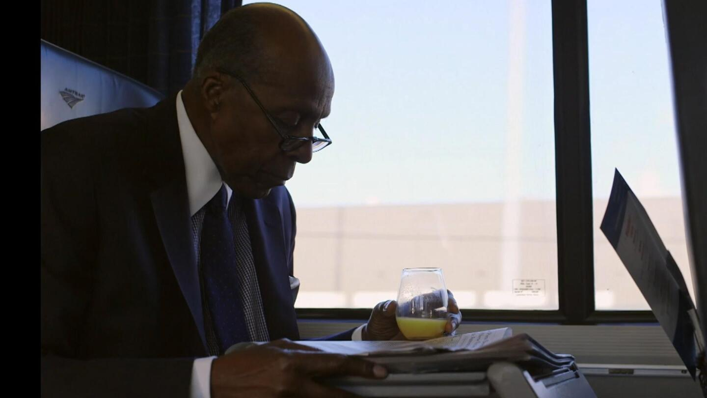 Vernon Jordan holds a glass of orange juice in his hand while reading the newspaper.