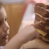 a small child counts the layers in a stack of sandwiches