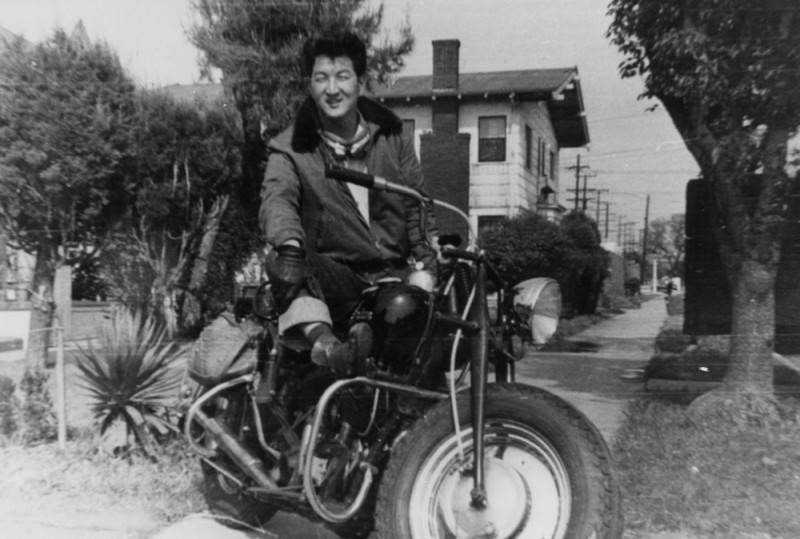 Black and white photo of a Korean American man posing next to a motorcycle.