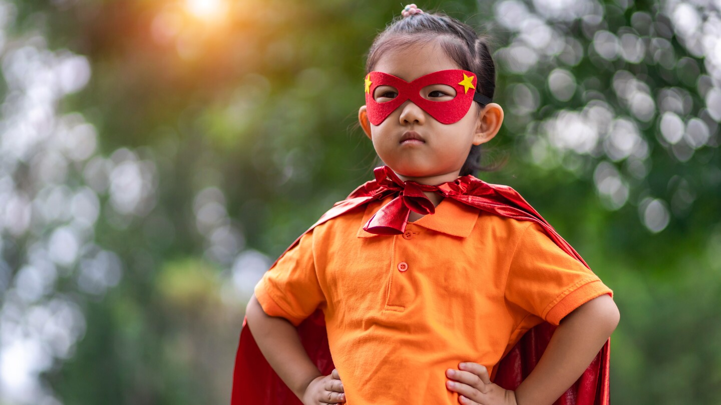 small Asian American child wearing a red mask and cape