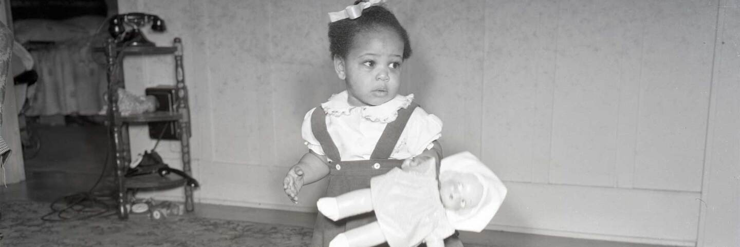 A little African American girl holding a doll | California State University Northridge