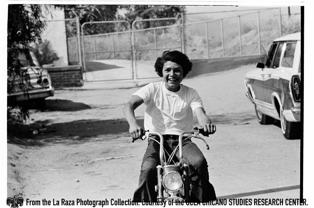CSRC_LaRaza_B16F6C10_Staff_012 Boy on a motorcycle | La Raza photograph collection. Courtesy of UCLA Chicano Studies Research Center
