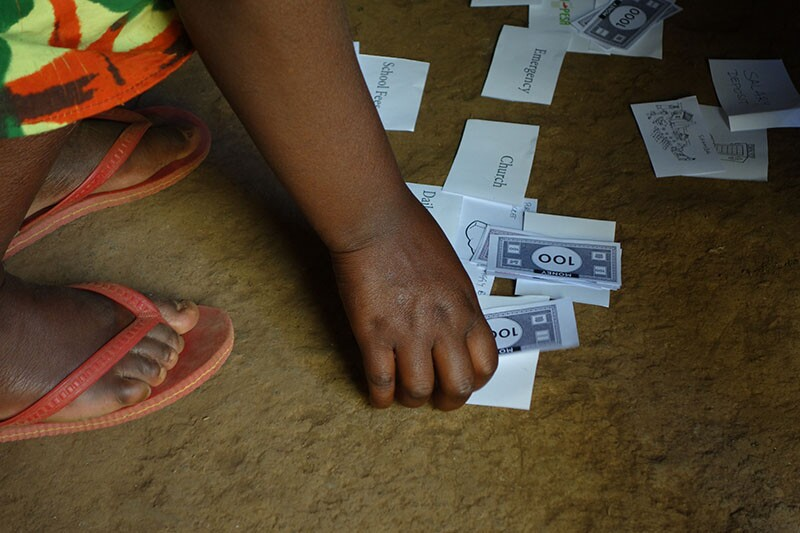 A young woman in Kenya demonstrates how she handles her finances using fake bills and flashcards. | Danny Alexander, IDEO.org