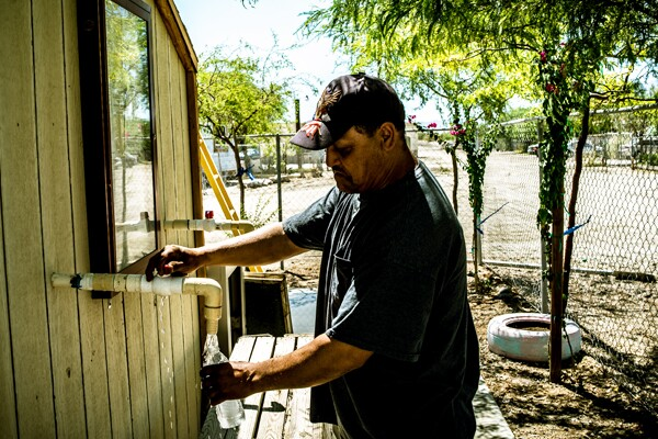 Roberto Mendez, a St. Anthony mobile home park resident and maintenance worker, fills his bottle at the on-site water station I Photo by Christian Mendez.