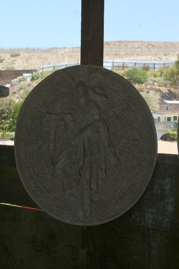 Hanging relief sculpture in Oscar's workshop is a combination of Jesus Helguera Aztec imagery and the Aztec calendar. The dual border fence can be seen in the background. | Photo: Misael Diaz.