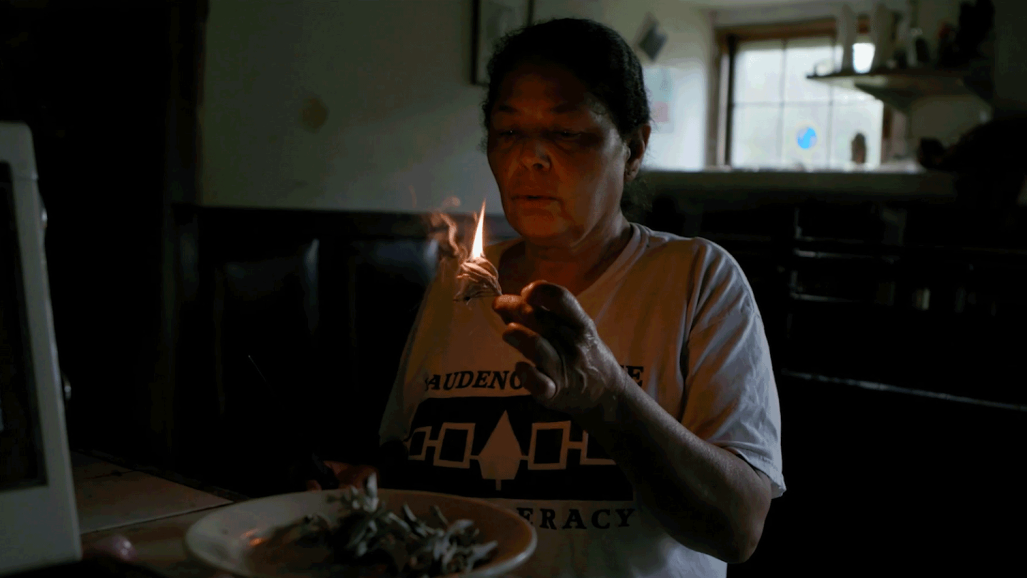 "A woman gently blows on a flame in a low lit room. | From ""Independent Lens: Conscience Point"""