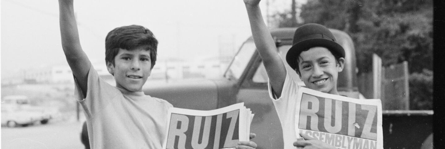 CSRC_LaRaza_B14F11C10_MB_013 Two young boys with their fists held high while holding newspapers in support of Raul Ruiz | Manuel Barrera, Jr., La Raza photograph collection. Courtesy of UCLA Chicano Studies Research Center