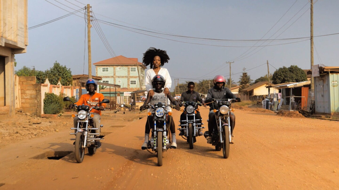 """Still from """"Come Meh Way:"""" Four men ride motorcycles through a dirt road, and a woman stands behind one of the men on a center motorcycle."""