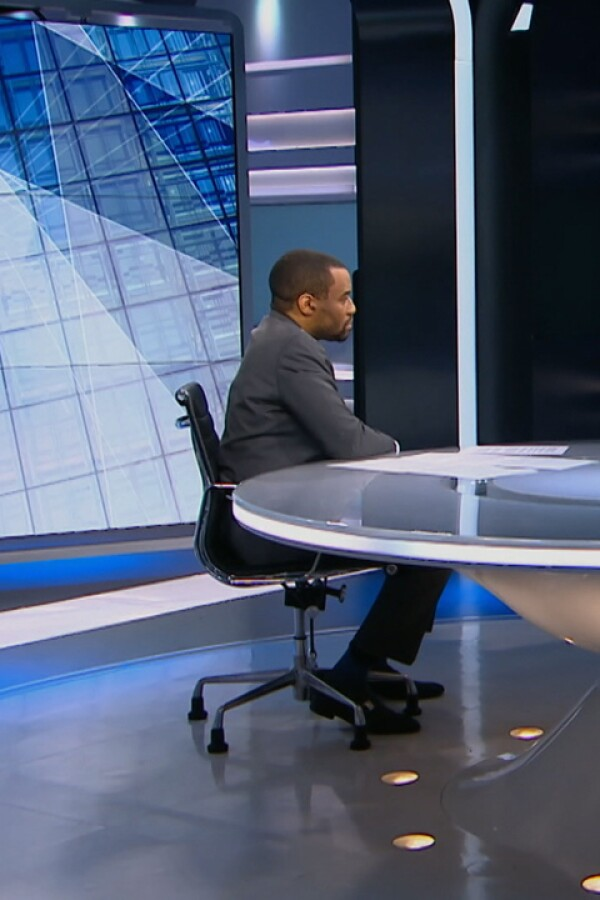 """Marc Lamont Hill sits behind a desk as he speaks to guests on video call on """"UpFront."""""""